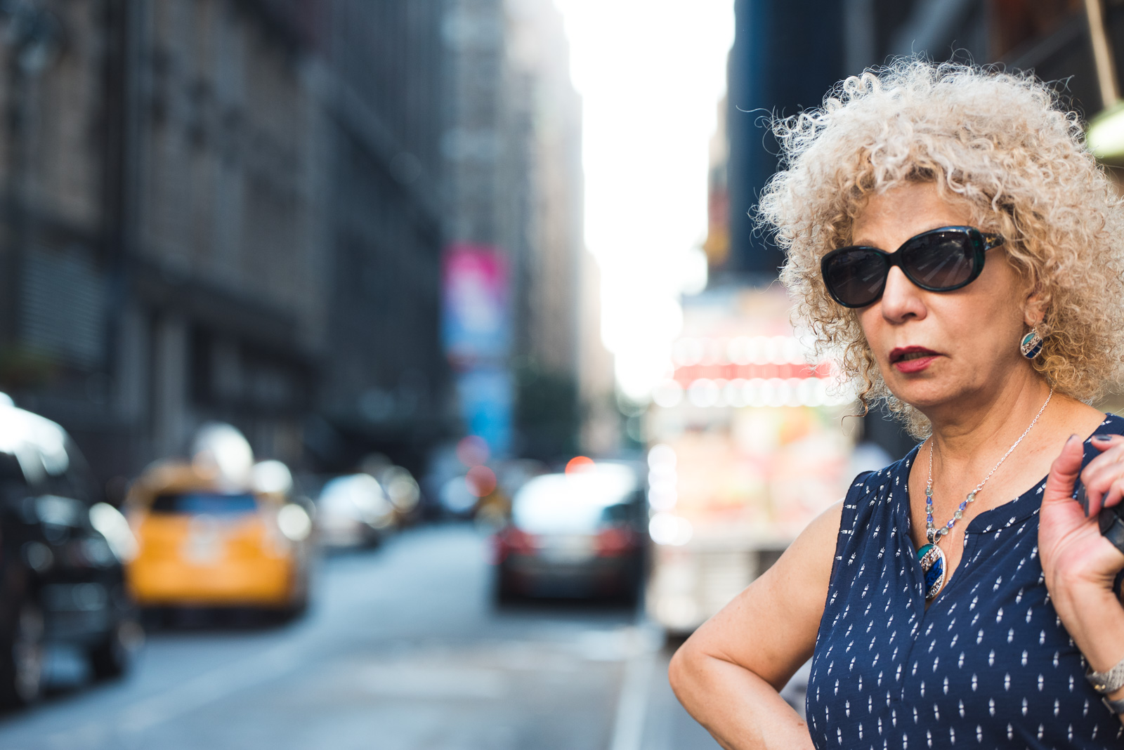 curly haired woman in a blue shirt standing by a busy street by Francesca Russell