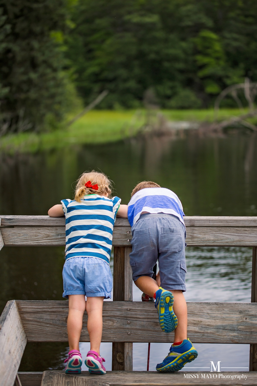 photo of children looking over a fishing dock by Missy Mayo