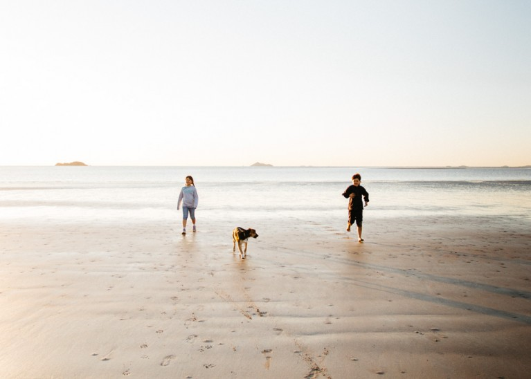 photo of two kids and a dog running on the beach by Jayne Cho