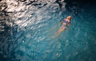 picture of girl relaxing in a pool by Elizabeth Blank