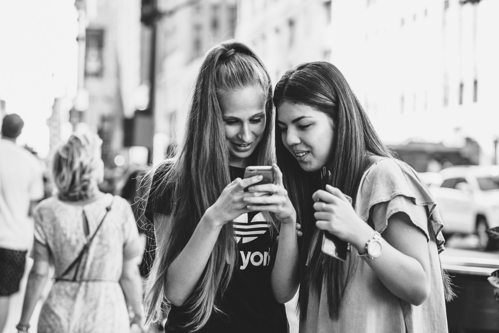 two girls looking at an iPhone by Francesca Russell