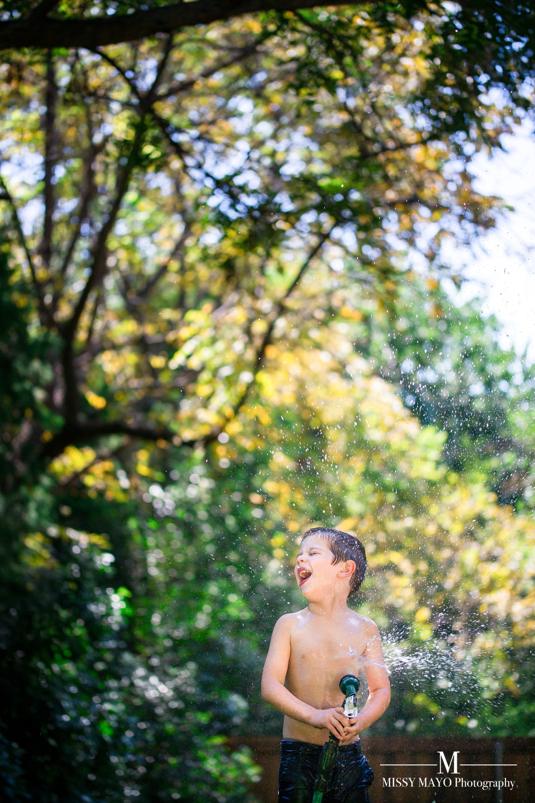 young boy spraying garden hose water on himself by Missy Mayo