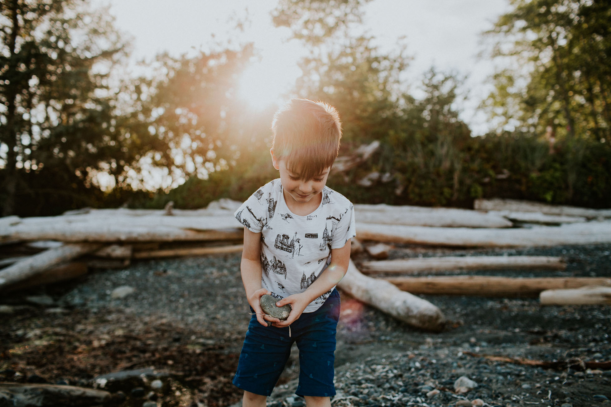 backlit picture of boy holding a rock by Cassandra Casley