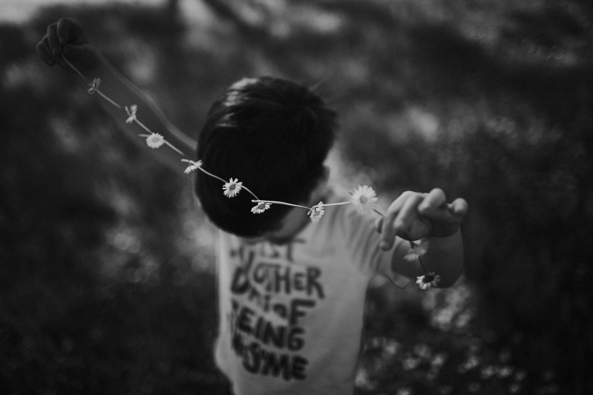 black and white photo of boy with a flower chain by Cassandra Casley