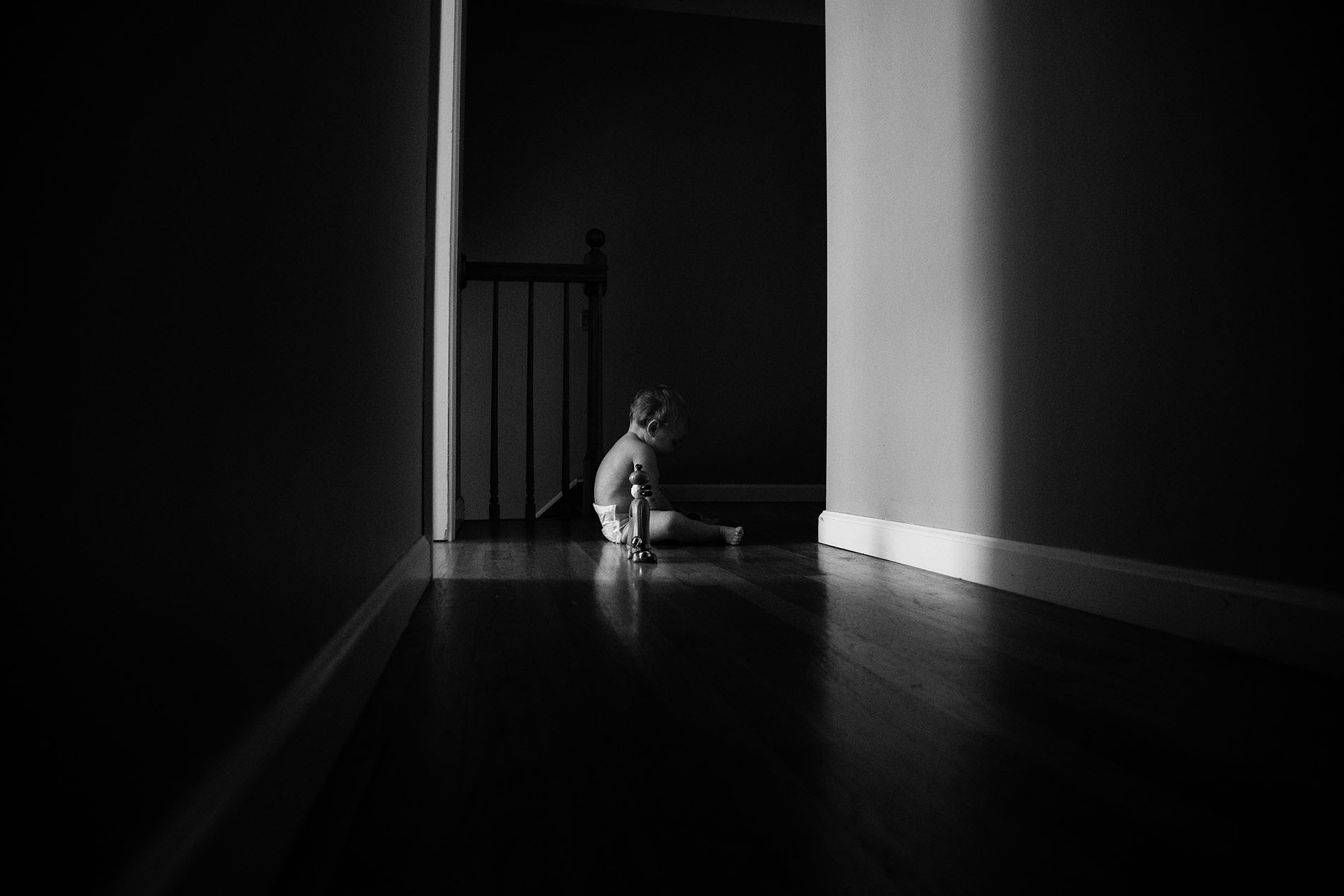 dark picture of kid sitting in the hallway by Jessica Svoboda