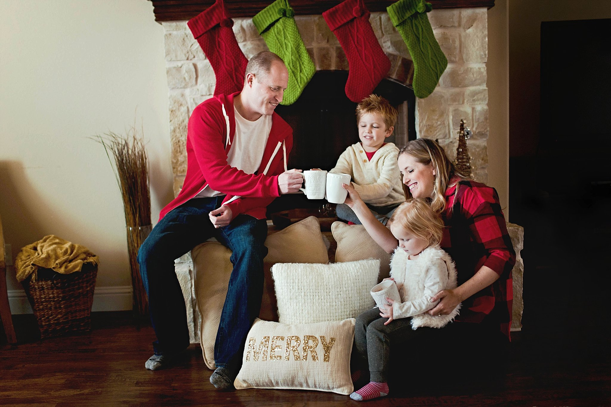 family Christmas photo by a fireplace by Erica Williams