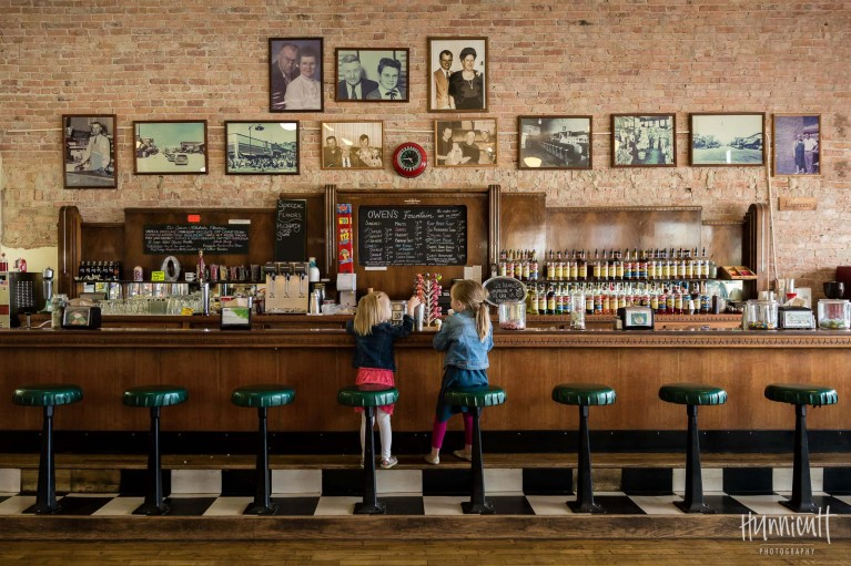 photo of girls sitting in a soda fountain shop by Rebecca Hunnicutt Farren
