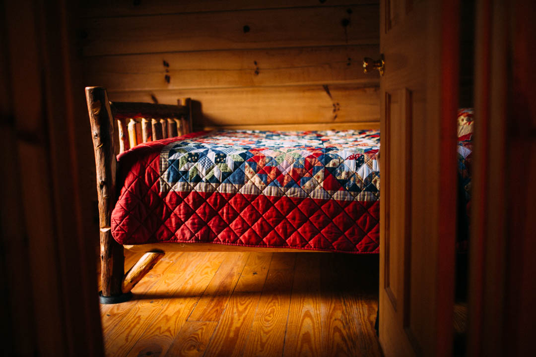 picture of quilt on a bed in a cabin by Ashley Maple