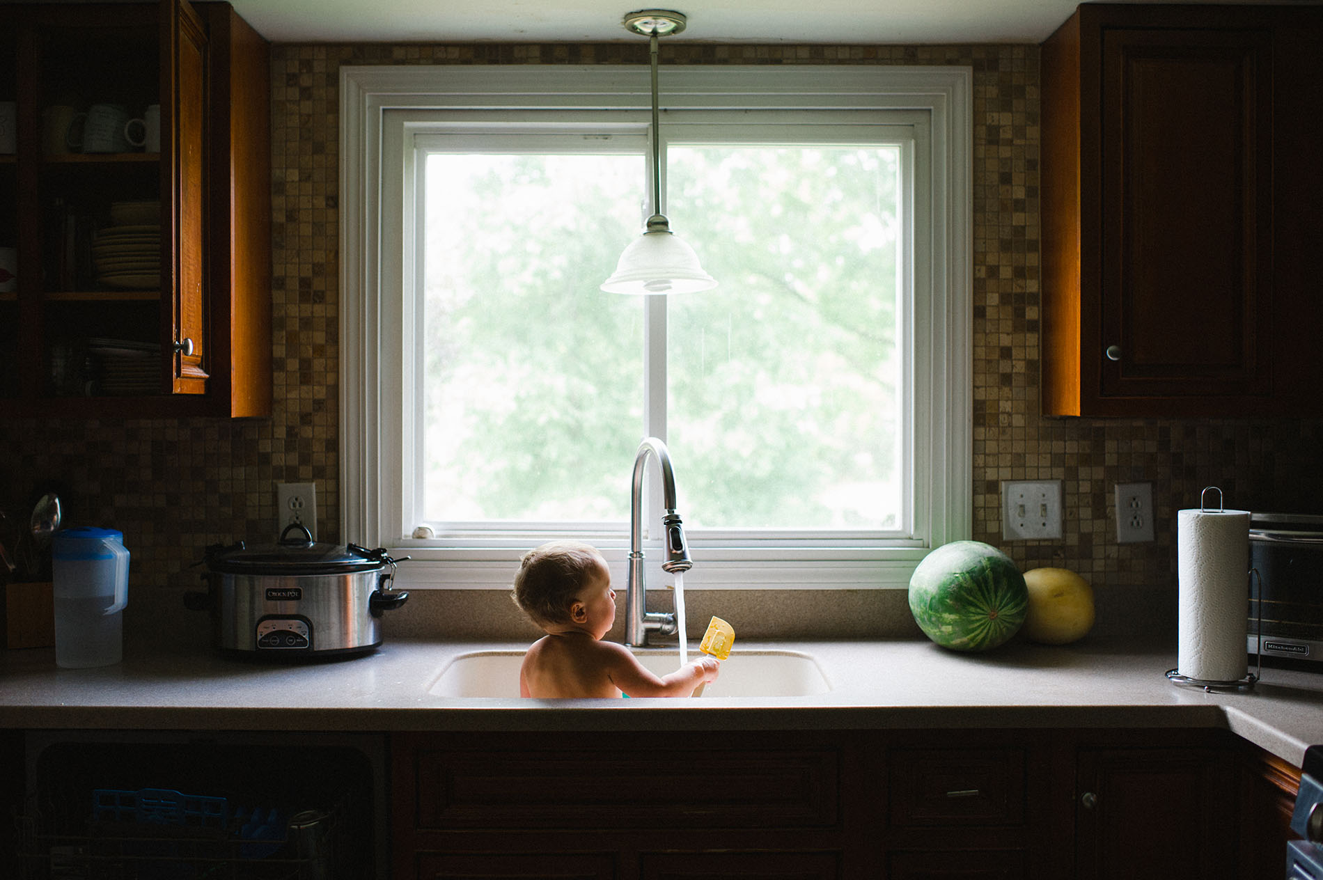 picture of toddler getting a sink bath by Jessica Svoboda