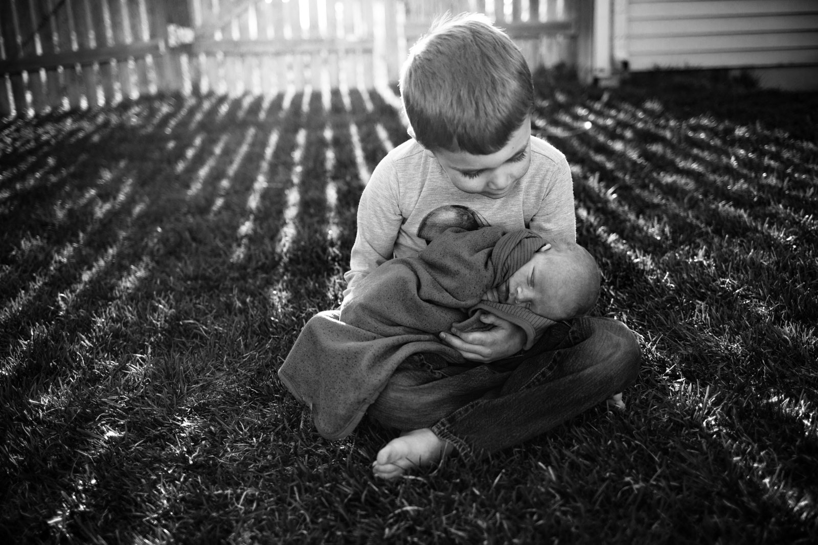 big brother holding little baby in yard by Sarah Rypma