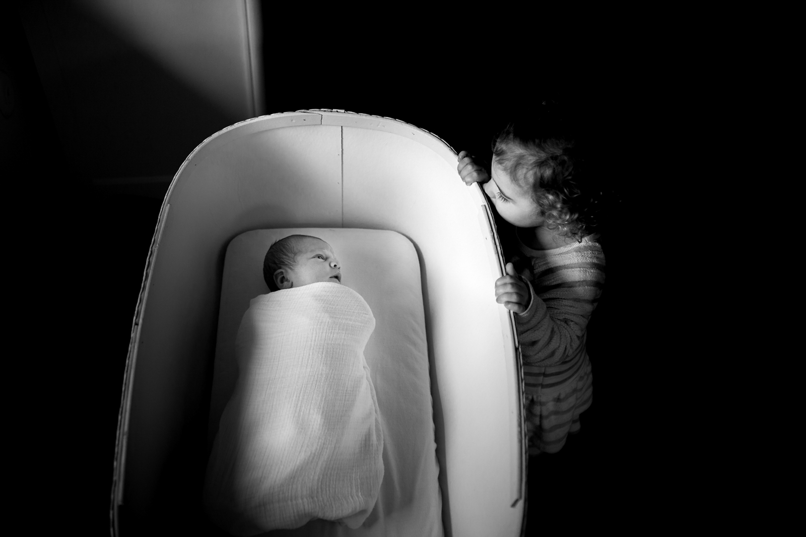 big sister looking at baby in bassinet by Sarah Rypma