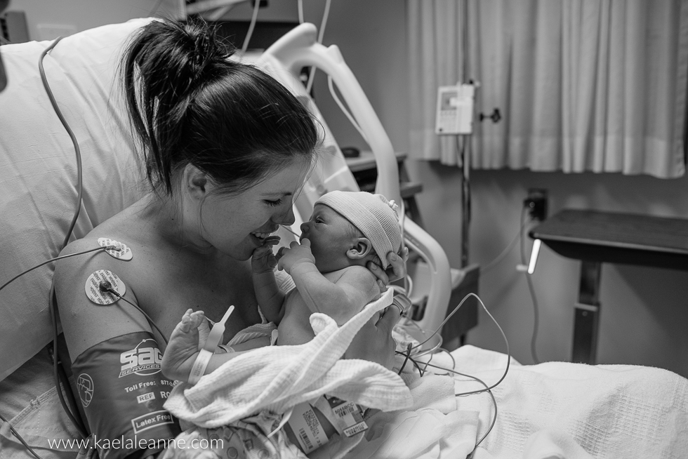 black and white pic of mom holding new baby in hospital by Kaela Elliott