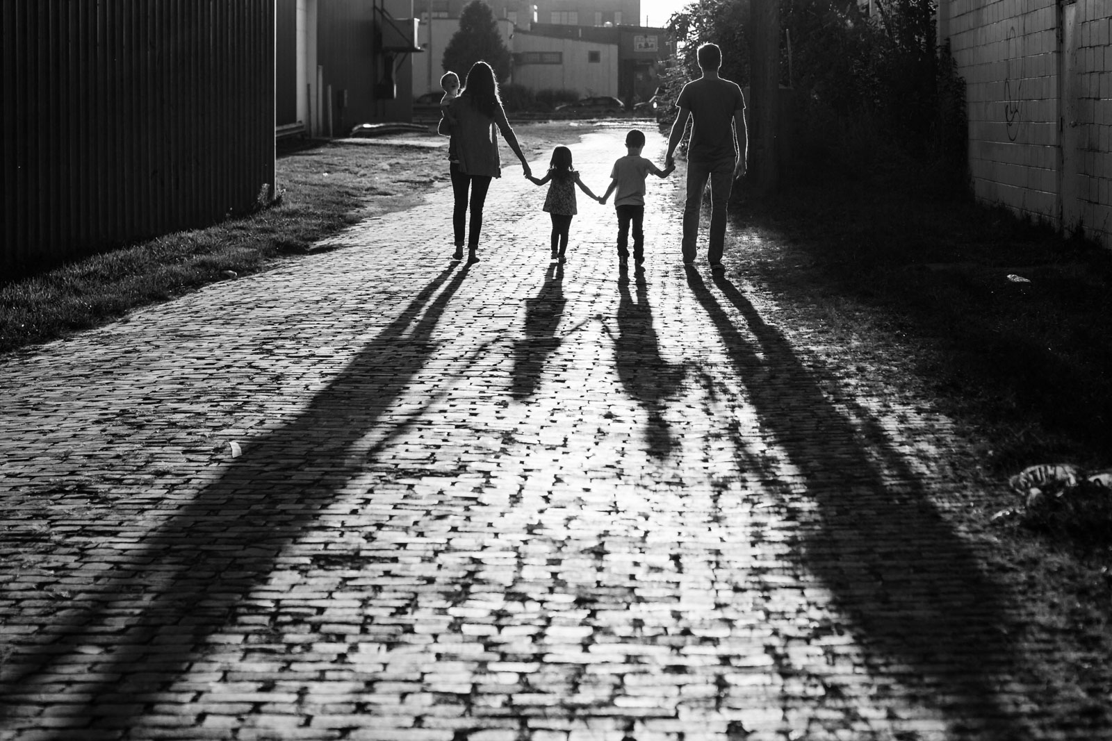 Backlit photo of family walking down a brick road by sarah rypma