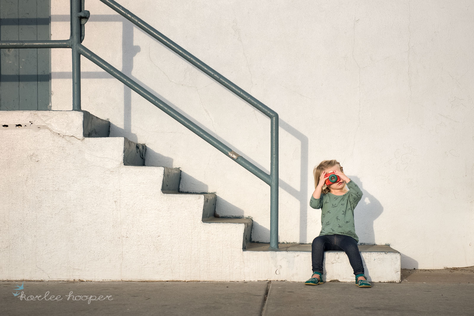 minimalist photo of a girl sitting on stairs with a camera by karlee