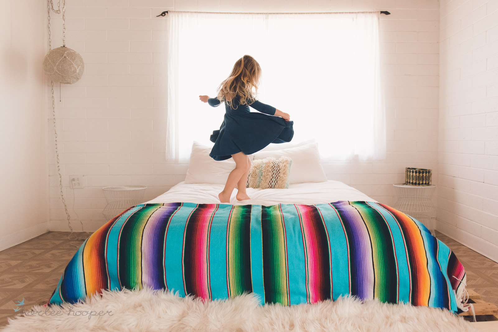 minimalist photo of a girl twirling on a bed in Alice and Ames dress by Karlee Hooper
