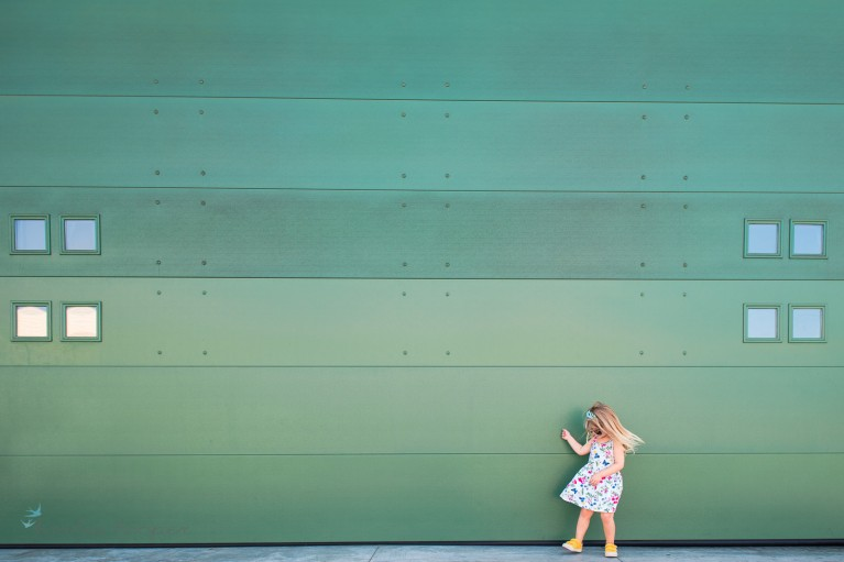 minimalist photo of a girl dancing with a green wall by Karlee Hooper