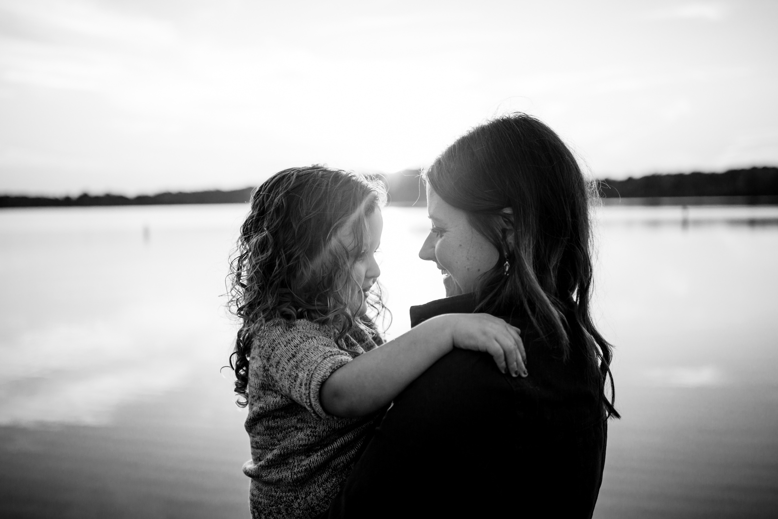 mom holding daughter by the water by Sarah Rypma