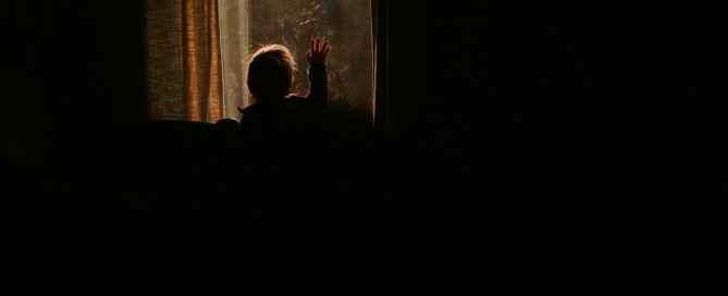 backlit photo of kid with hand against window by Bethany Sams
