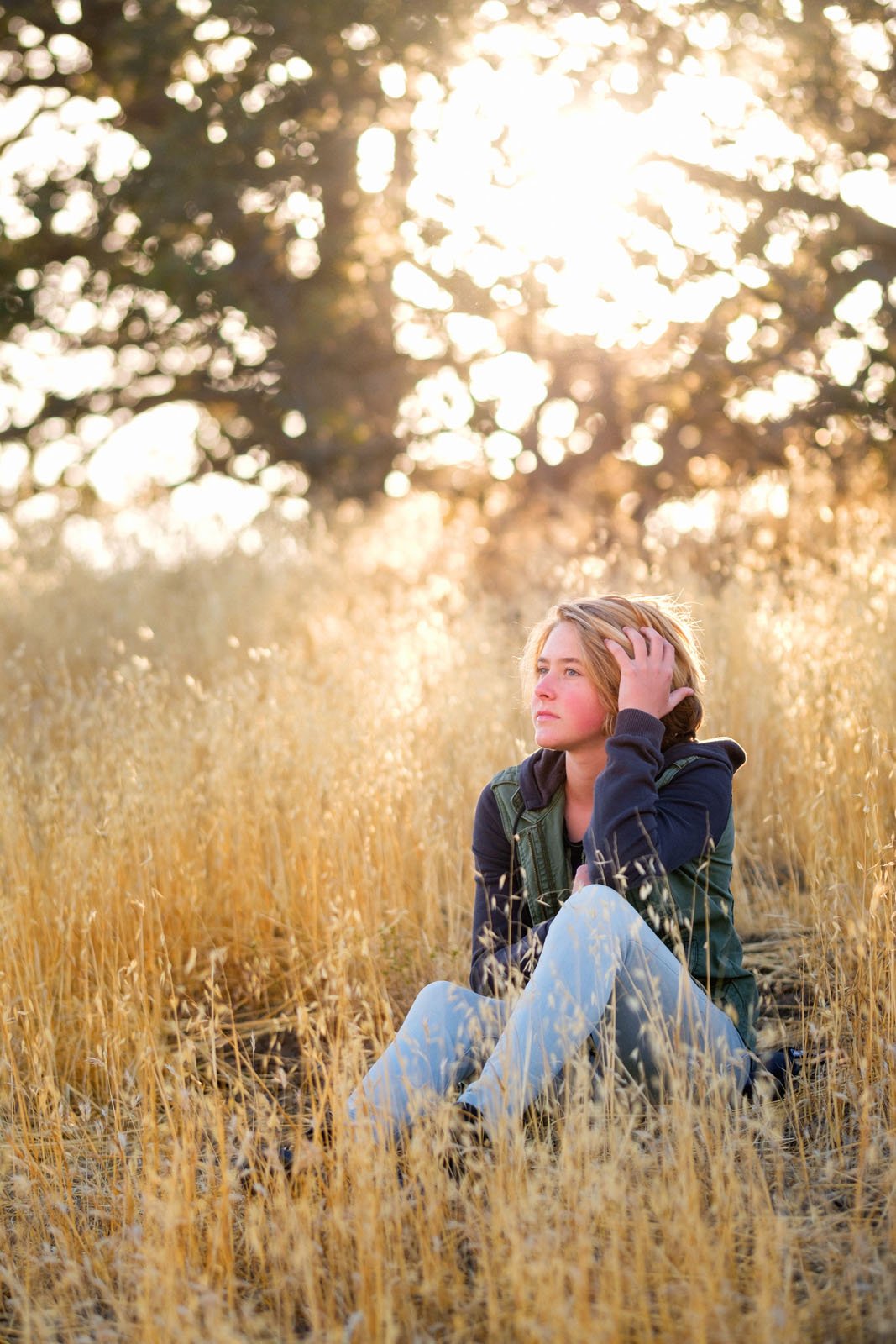 backlit photo of teen girl sitting in a field by California photographer Michelle Turner