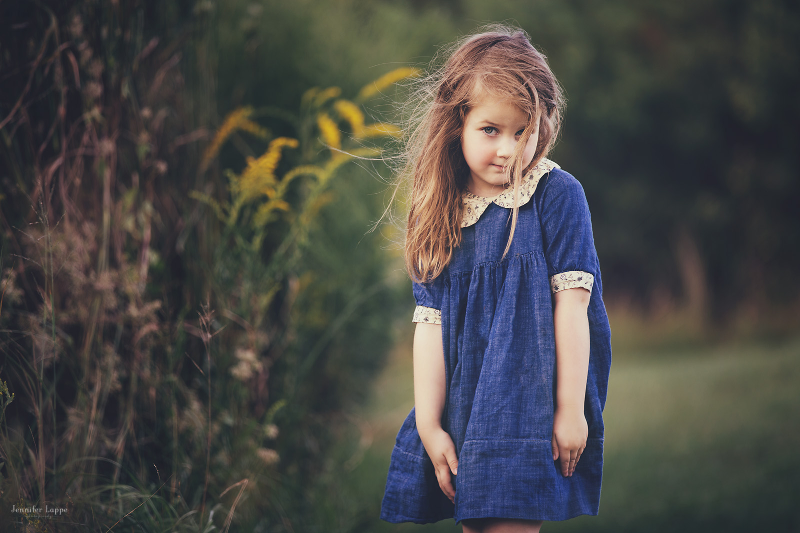 outdoor picture of girl looking at camera in a blue dress by Jennifer Lappe