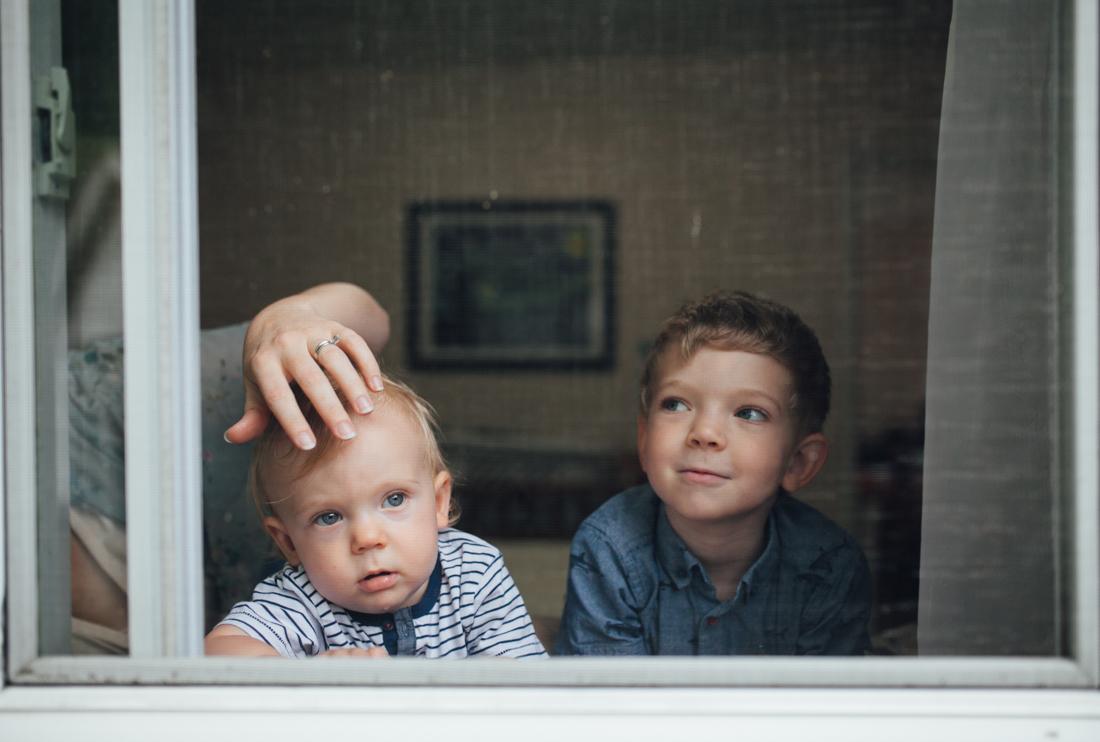 two kids looking out a window by Juliette Fradin