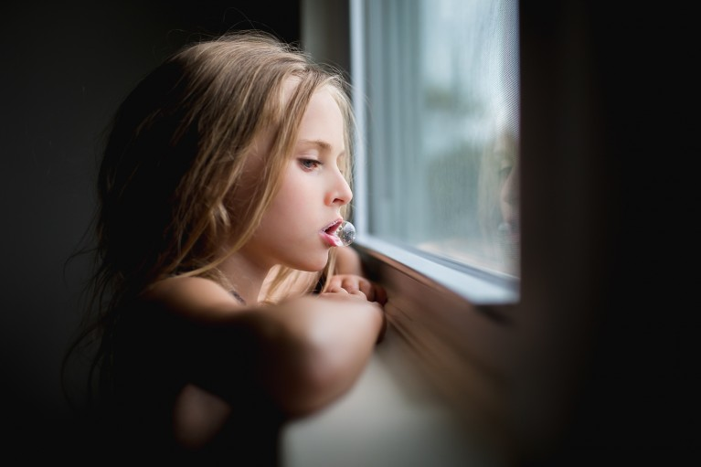 window light photo of girl blowing a bubble by Jessica Orlowicz
