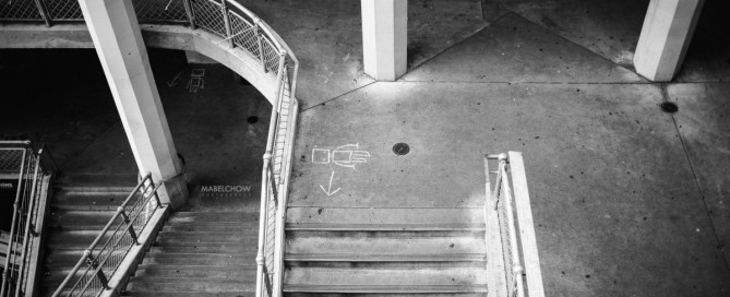 black and white photo of parking garage stairs by Mabel Chow
