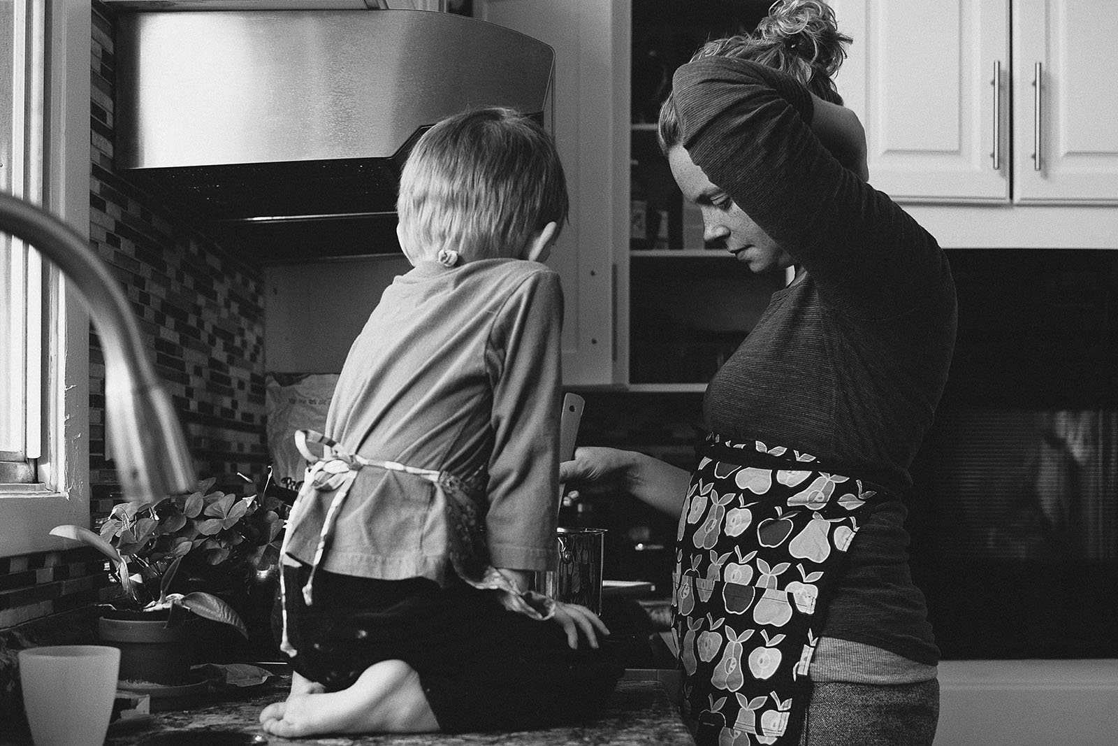 black and white pic of mom and son cooking by Sarah Lalone