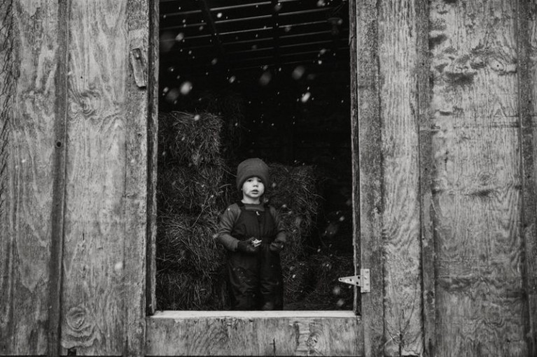 black and white picture of boy looking out the window at falling snow by Ashley Manley