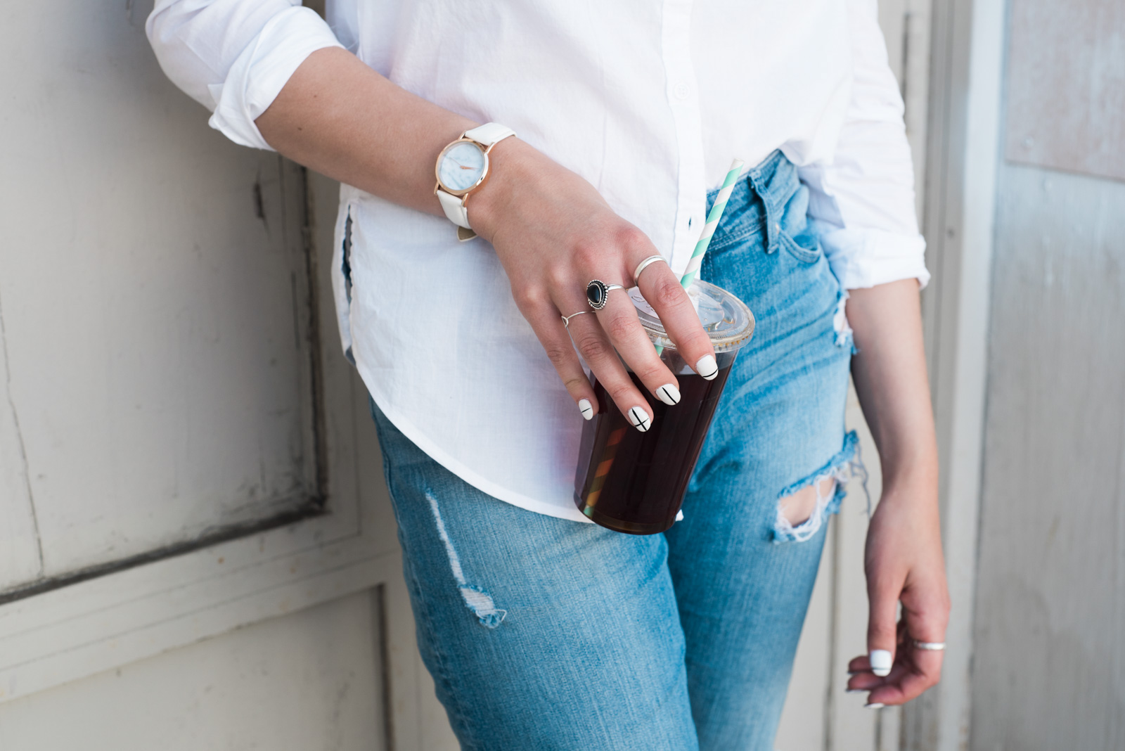 stock photo of woman holding a to go drink by Jana Bishop