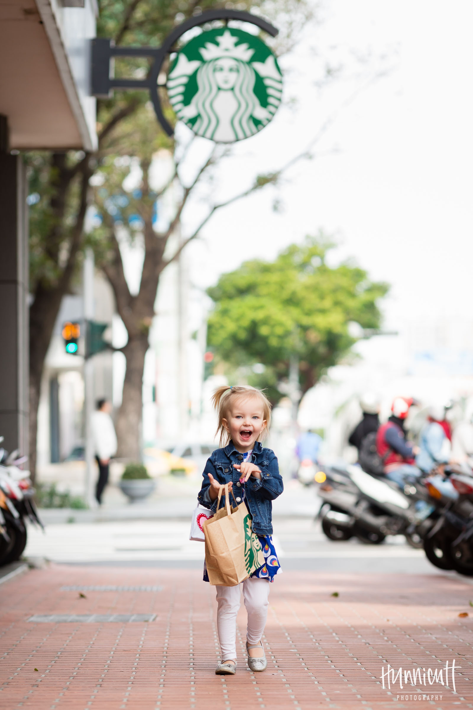 smiling girl carrying a Starbucks sack by Rebecca Hunnicutt Farren