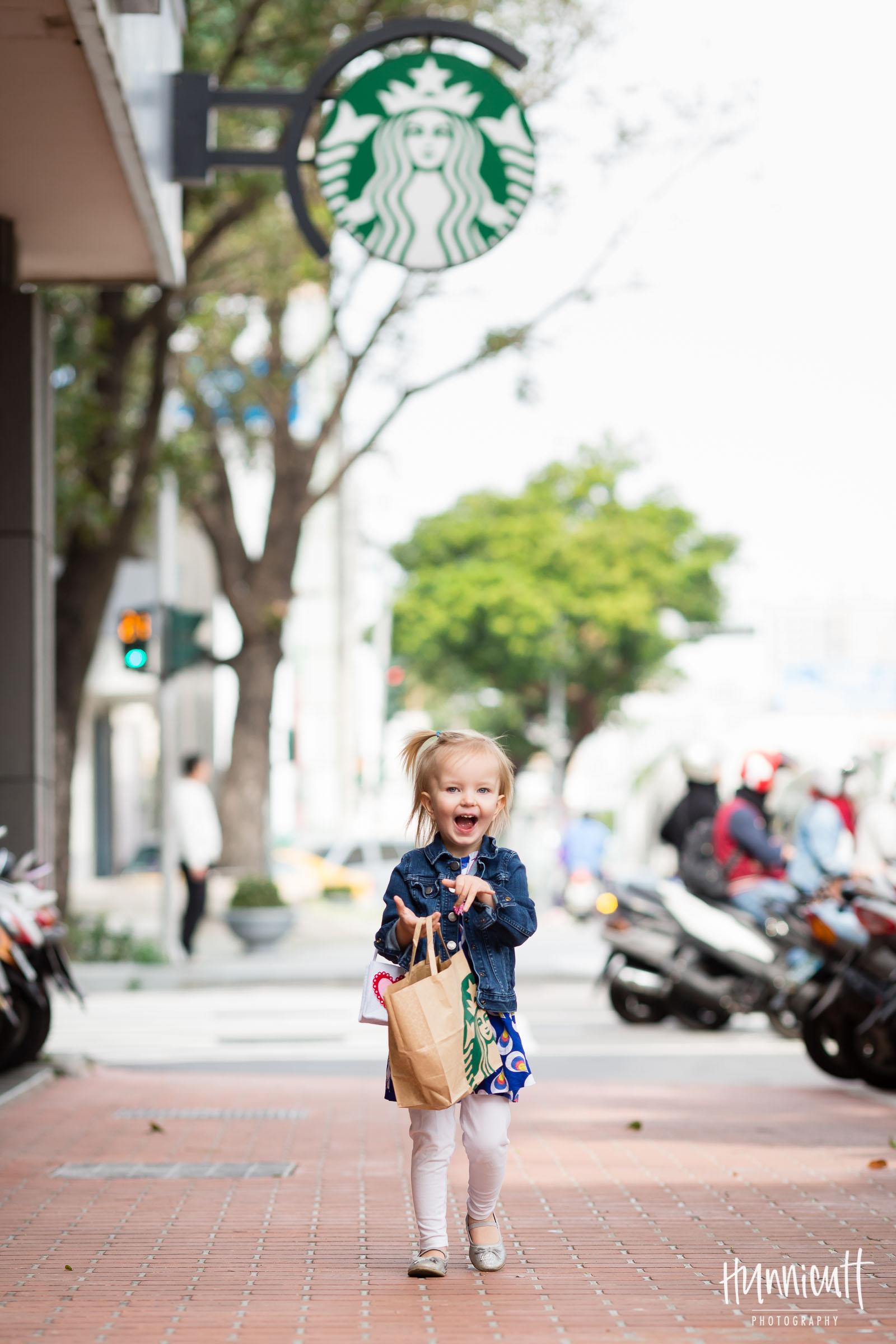 smiling girl carrying a Starbucks sack by Rebecca Hunnicutt Farren