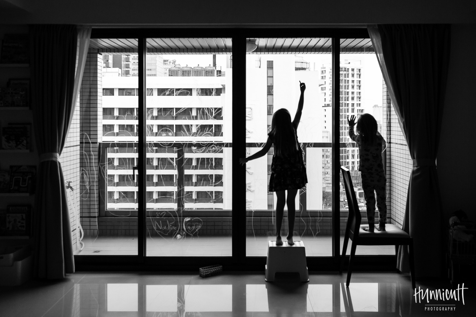 black and white photo of girls coloring on windows by Rebecca Hunnicutt Farren