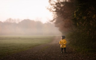 photo of boy in a yellow raincoat walking in the fog by Danielle Awwad