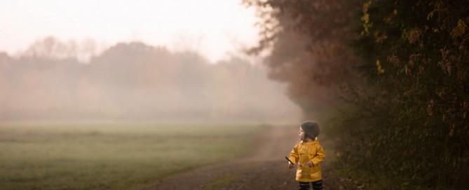 photo of boy in a yellow raincoat walking in the fog by Danielle Awwad