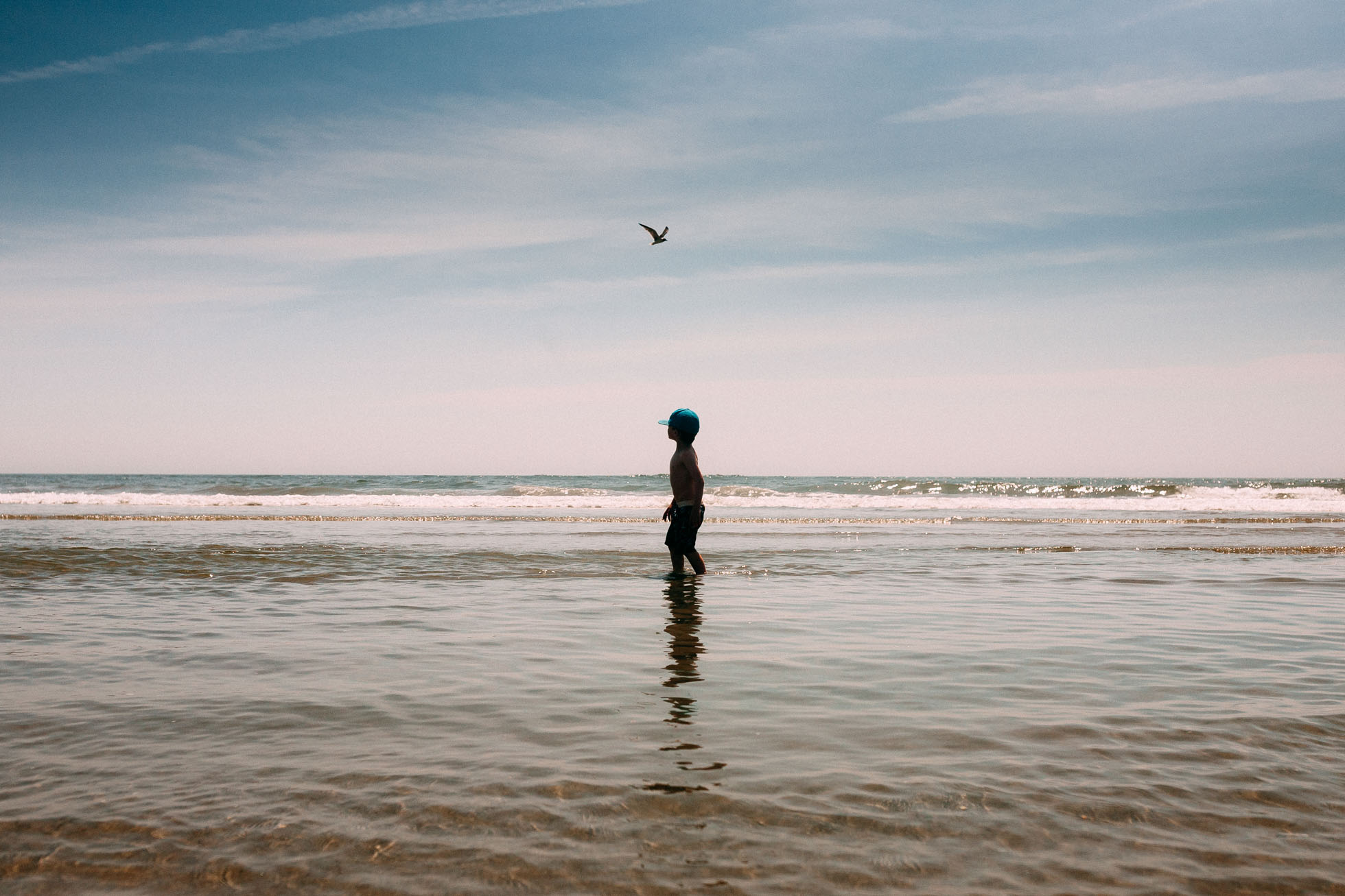 photo of boy in the water with a bird flying in the sky by Sonia Bourdon