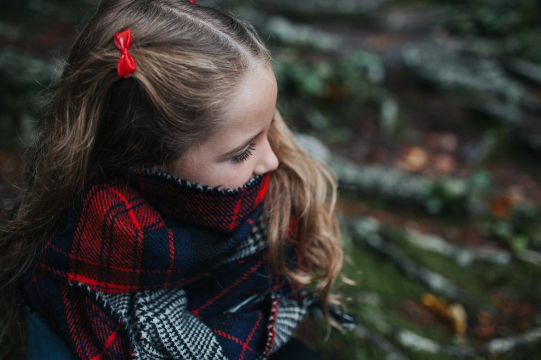 pic of girl wearing a red bow snuggled up to stay warm outside by Beth Crossman