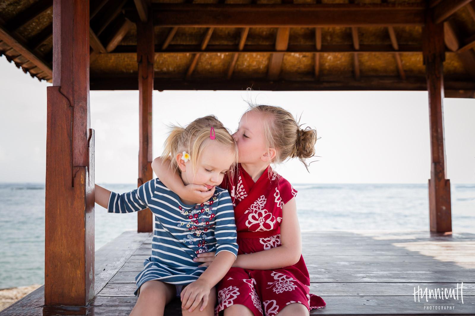 sisters sitting on a dock in Bali hugging by Rebecca Hunnicutt Farren