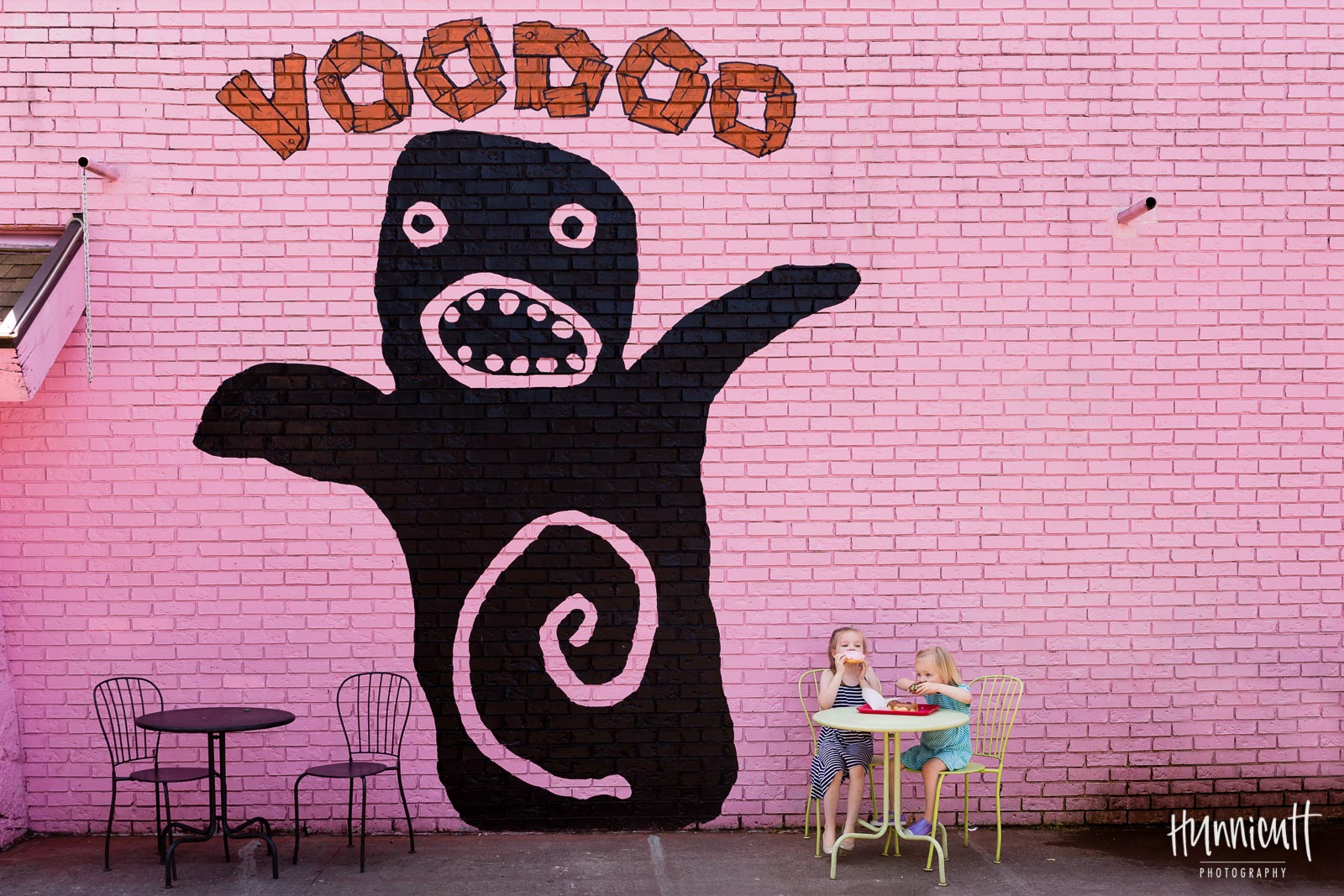 sisters enjoying donuts at voodoo by pink wall in portland by Rebecca Hunnicutt Farren