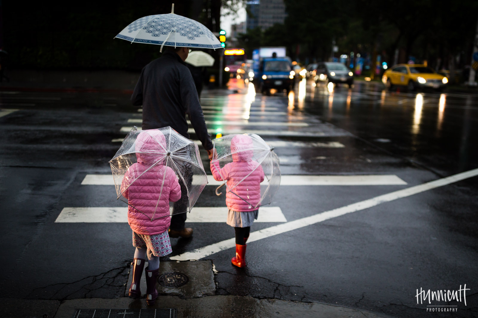 pic of girls in pink coats crossing the street in the rain by Rebecca Hunnicutt Farren