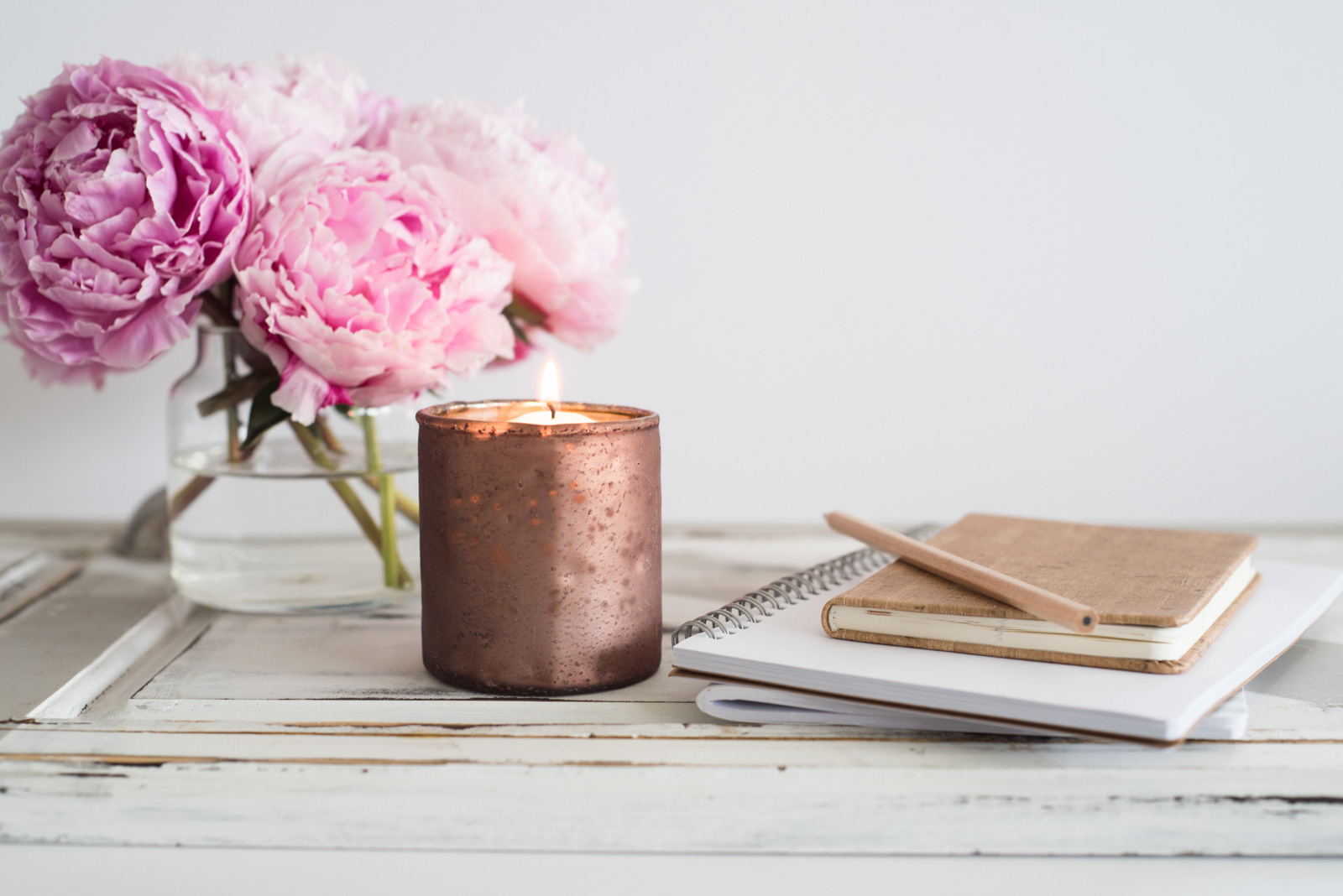 stock photo of gold candle and a vase of pink carnations by Jana Bishop