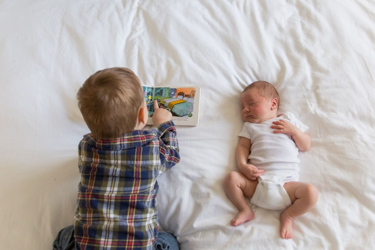 photo of brother reading to newborn by Jaye McLaughlin
