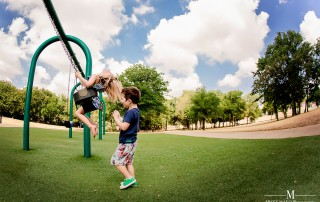 picture of boy pushing his sister on a swing by Missy Mayo