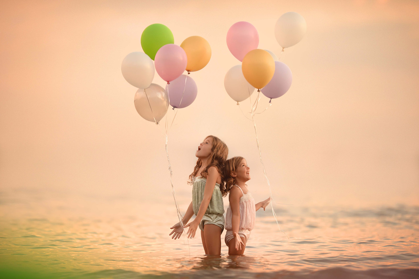 Photo of two girls in the water with balloons by beth wade