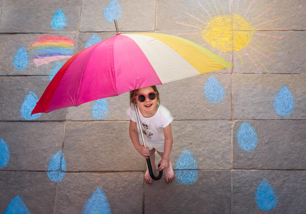 Girl with an umbrella on a sidewalk with chalk