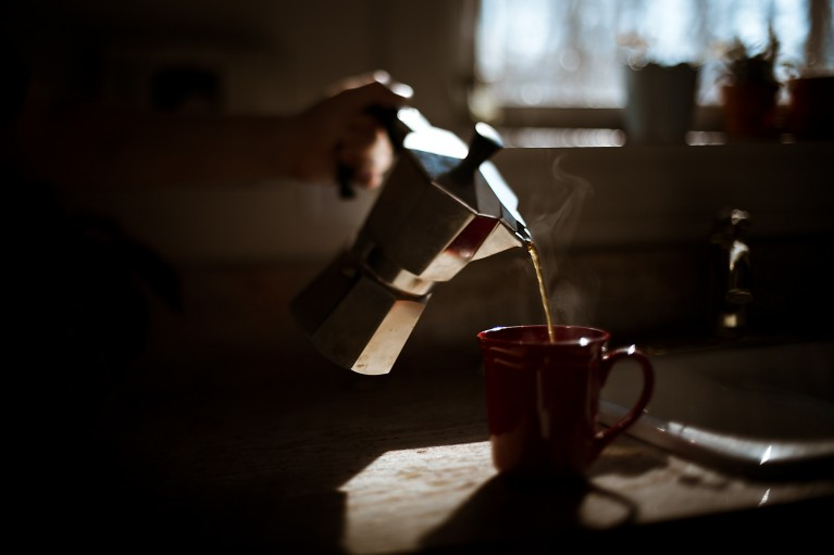 A low-light picture of a hand pouring coffee in front of a window.