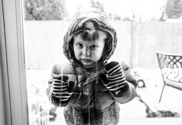 finding inspiration in bad weather, a boy in winter gear looks in a window