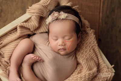 example of rembrandt light, baby lays in wooden box in studio