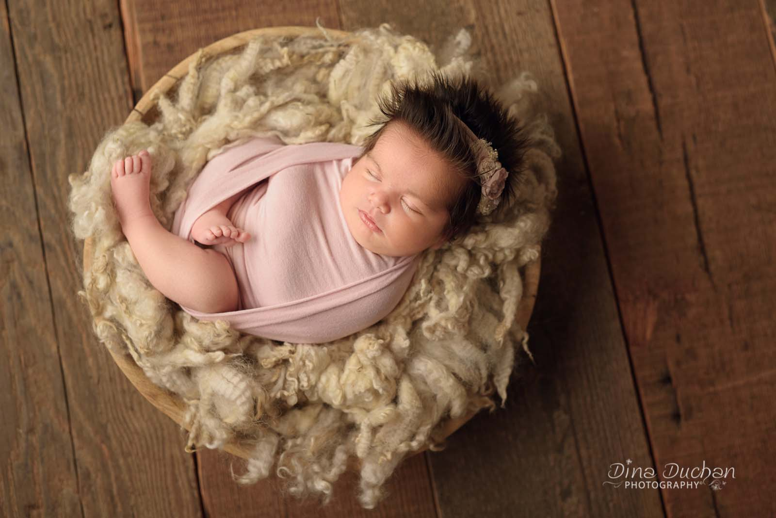 Newborn in basket with studio lighting