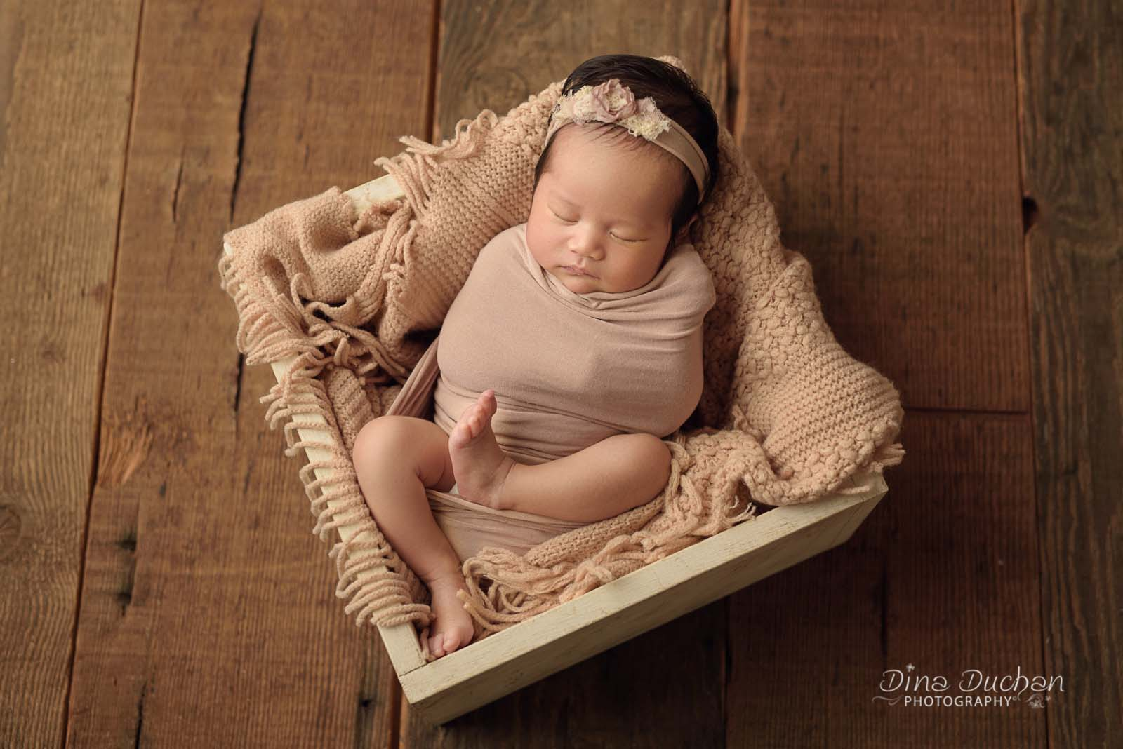 example of bad pose for newborn photo with studio lighting, baby laying in straight line